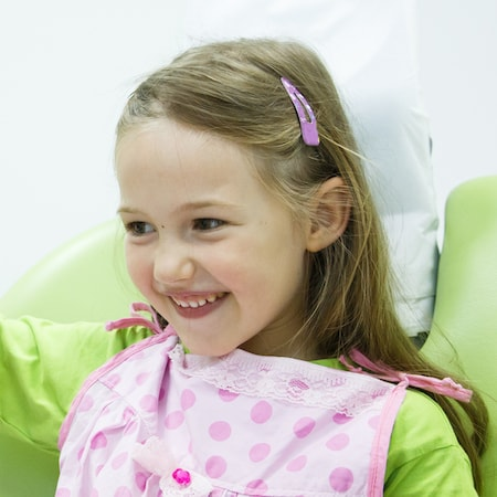 Little girl wearing a pink bib during her children's dentistry visit
