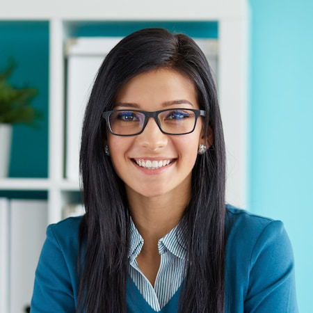 Woman wearing glasses and a blue top in front of a blue background