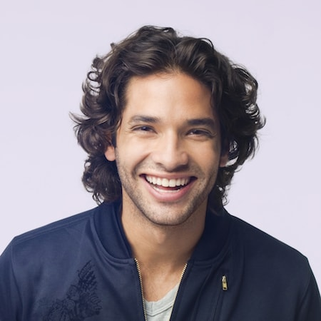 Young man smiling with long hair after he has received a root canal