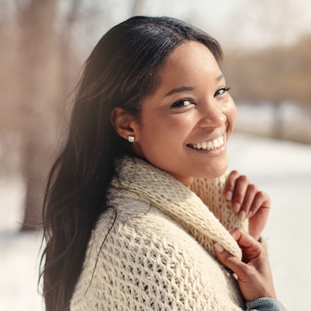 Smiling woman looking back and wearing a thick sweater