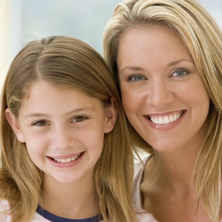 Light-haired mother and daughter smiling
