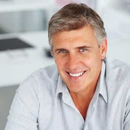 Older man wearing a grey shirt and smiling thanks to an inlay