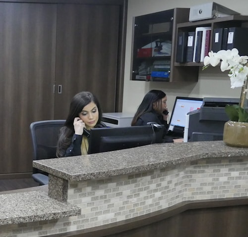 Our front desk team working on the phones speaking to new patients and insurance companies