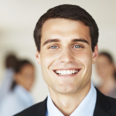 Young business man smiling in a suit after receiving a new dental bridge