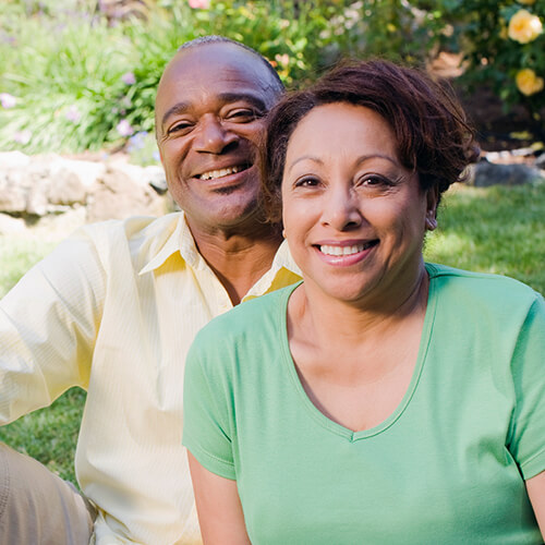 A senior man and woman smiling to the camera because of the restorative dentistry services offered by their dentist in White Plains, NY