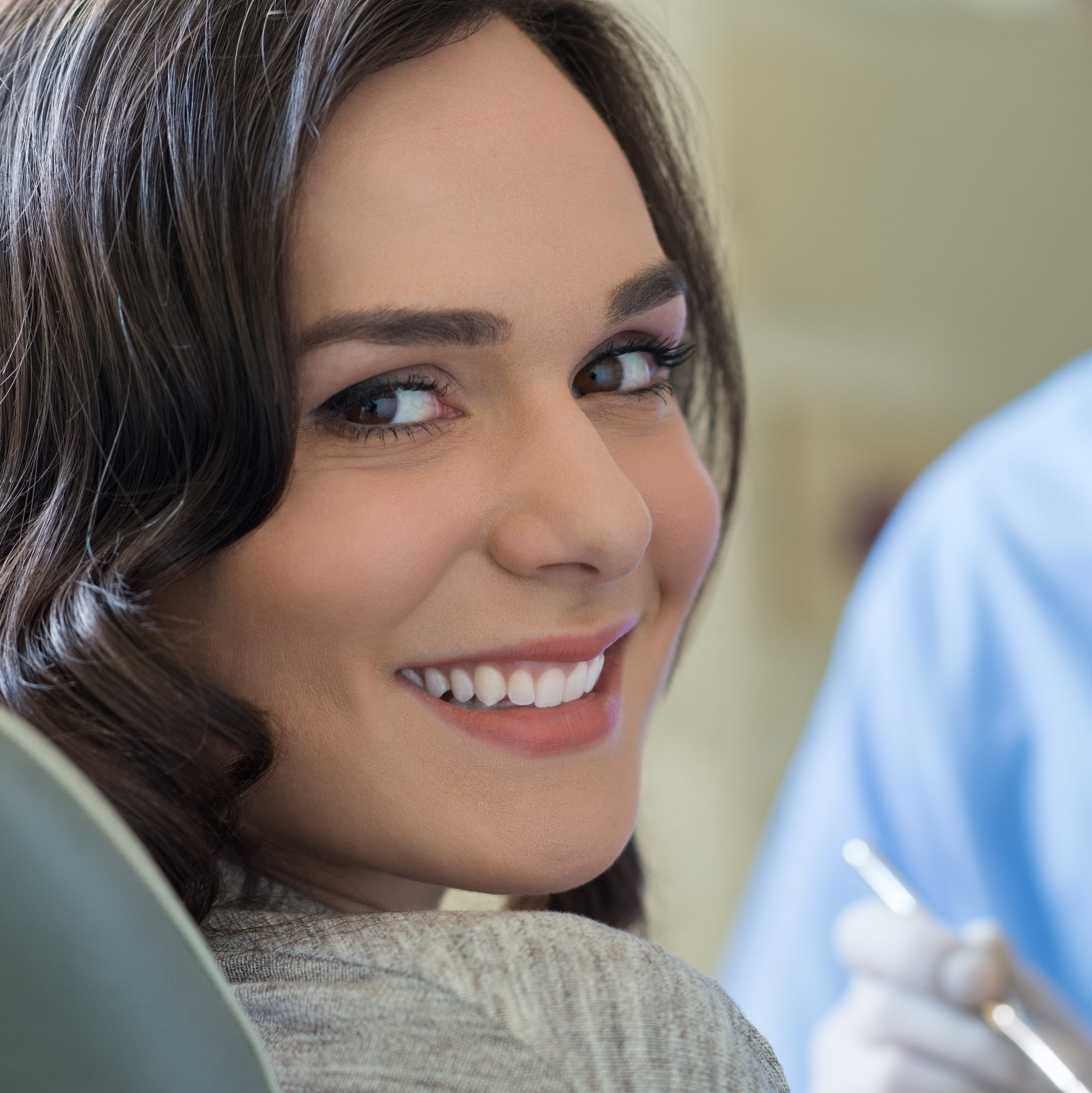 Smiling woman in dental chair looking back over her shoulder.